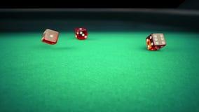 三个在绿色比赛赌博的桌上的红色模子辗压在黑背景,射击与慢动作,体育休闲的概念 影视素材