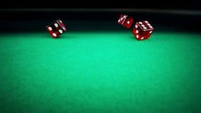 三个在绿色比赛赌博的桌上的红色模子辗压在黑背景,射击与慢动作,体育休闲的概念 股票视频