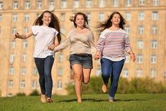 三个在草和暂挂现有量的微笑的女孩运行 免版税库存照片