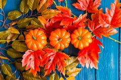 三个塑料南瓜和叶子秋天概念 图库摄影