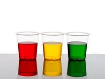三个塑料杯子饮料-红色黄色和绿色 库存照片