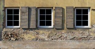 三个塑料白色窗口以黄色涂了灰泥a墙壁  免版税库存照片