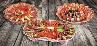 三个塞尔维亚传统受欢迎的开胃菜美味盘在老破裂的剥落的庭院表上显示的Meze的汇集 图库摄影