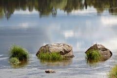 三个大岩石在有强的流程的一条河 免版税图库摄影