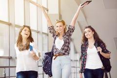 三个女孩努力去做与他们的行李在机场并且笑 与朋友的一次旅行 免版税库存照片