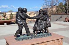 三个女孩和两个男孩铜雕塑  库存照片