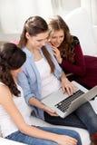 三个女孩和膝上型计算机 免版税图库摄影