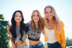 三个女孩在夏天公园走 库存照片