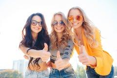 三个女孩在夏天公园走 库存图片