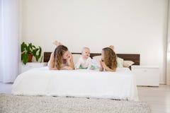 三个女孩在床上的早晨演奏姐妹在卧室 库存照片