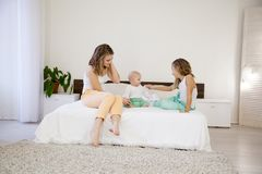 三个女孩在床上的早晨演奏姐妹在卧室 库存图片