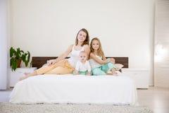 三个女孩在床上的早晨演奏姐妹在卧室 免版税图库摄影