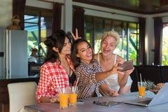 三个女孩在拍Selfie照片坐细胞巧妙的电话愉快微笑,少妇朋友的表上摆在  免版税库存照片