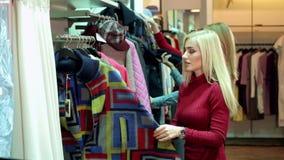 三个女孩在服装店走,他们看衣裳并且试穿它 股票录像