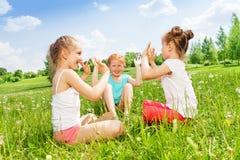 三个女孩坐一个美妙的草甸 库存图片