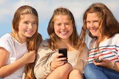 三个女孩坐与移动电话和微笑 免版税图库摄影