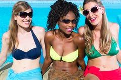 三个女孩坐在夏天放松的游泳池 免版税图库摄影