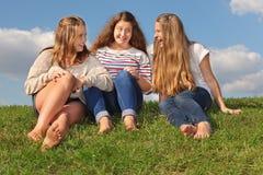 三个女孩坐在草、聊天和笑 免版税库存照片