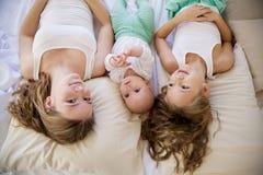 三个女孩姐妹早晨在卧室醒了 库存照片