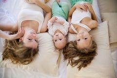 三个女孩姐妹早晨在卧室醒了 免版税库存图片