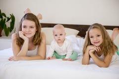 三个女孩姐妹早晨在卧室 免版税库存照片