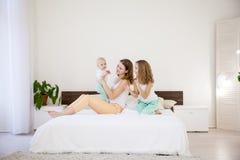 三个女孩姐妹早晨在卧室 库存照片