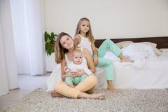 三个女孩姐妹早晨醒了在床上的卧室 库存图片
