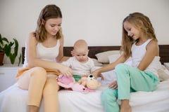 三个女孩姐妹早晨醒了在床上的卧室 免版税图库摄影
