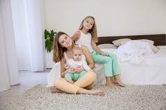 三个女孩早晨使用在卧室 免版税库存照片