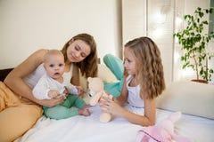 三个女孩早晨使用在卧室 免版税库存图片