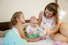 三个女孩早晨使用在卧室 免版税图库摄影