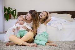 三个女孩早晨演奏姐妹在卧室 免版税库存照片