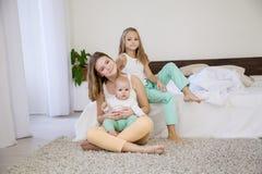三个女孩早晨演奏姐妹在卧室 库存图片