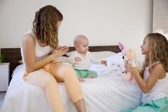 三个女孩早晨演奏姐妹在卧室 免版税库存图片