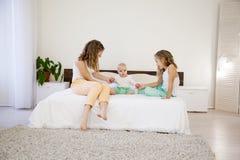三个女孩早晨演奏姐妹在床上的卧室 免版税库存图片