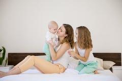 三个女孩早晨演奏姐妹在床上的卧室 免版税图库摄影