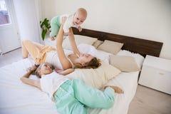 三个女孩早晨演奏姐妹在床上的卧室 库存照片