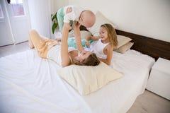 三个女孩早晨演奏姐妹在床上的卧室 免版税库存照片