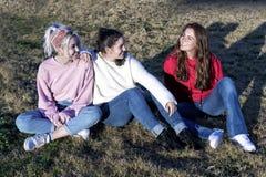 三个女孩画象获得乐趣在日落在公园ina好日子 免版税库存图片