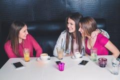 三个女孩获得乐趣在咖啡馆 免版税库存图片