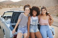 三个女性朋友画象在经典汽车后车箱坐旅行 库存图片