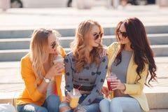三个女朋友坐步在公园 免版税库存照片