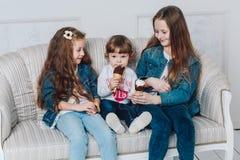 三个妹在家一起吃冰淇凌 免版税库存照片
