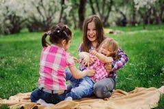 三个妹获得一起演奏室外的很多乐趣在夏天公园在度假 免版税图库摄影