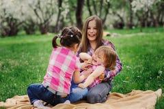 三个妹获得一起演奏室外的很多乐趣在夏天公园在度假 免版税库存照片