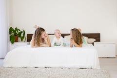 三个姐妹的孩子在床上的早晨在卧室 库存图片