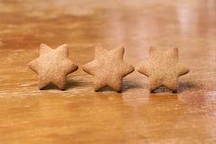 三个姜曲奇饼 形状星 被弄脏的背景 免版税库存图片