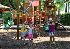 三个孩子在夏天享用操场 库存图片