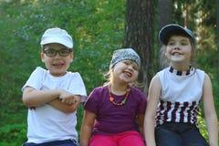 三个孩子在夏天坐,微笑和鬼脸 库存图片