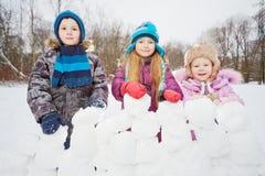 三个孩子在雪砖做的墙壁后站立 库存图片